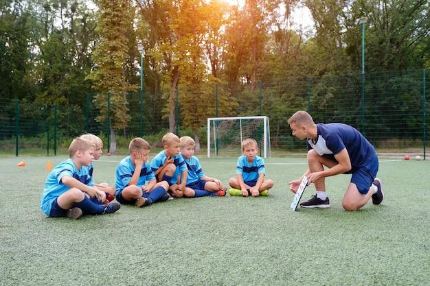 Entrenador joven con portapapeles enseña a los niños la estrategia que juega en el campo de fútbol. Foto Premium