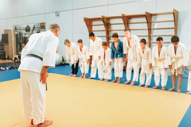 Entrenador y niños en uniforme, entrenamiento de judo para niños. jóvenes luchadores en gimnasio, artes marciales, estilo de vida saludable Foto Premium