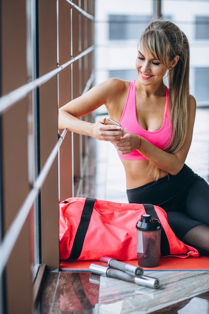 Entrenador de yoga femenino usando el teléfono Foto gratis