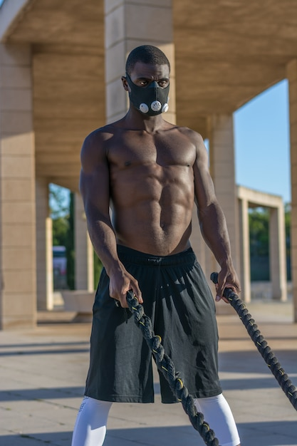 Entrenamiento muscular masculino con cuerdas de combate y máscara de entrenamiento. Foto Premium