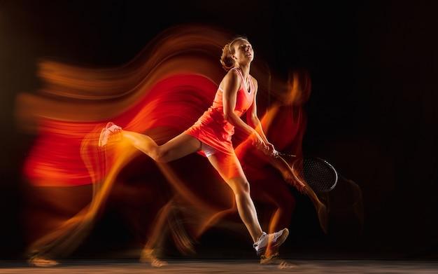 Entrenamiento de tenista profesional aislado sobre fondo negro de estudio en luz mixta. mujer en traje deportivo practicando. Foto gratis