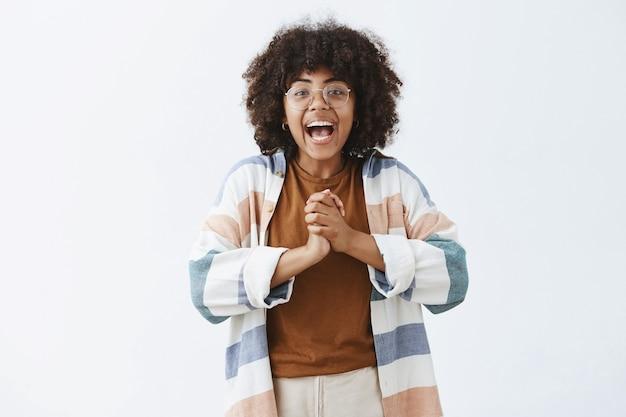 Entusiasta, activa y despreocupada, chica optimista de piel oscura con gafas y un atuendo elegante, juntando las manos cerca del pecho y sonriendo ampliamente, emocionada con una gran noticia contándola al resto de la gente. Foto gratis