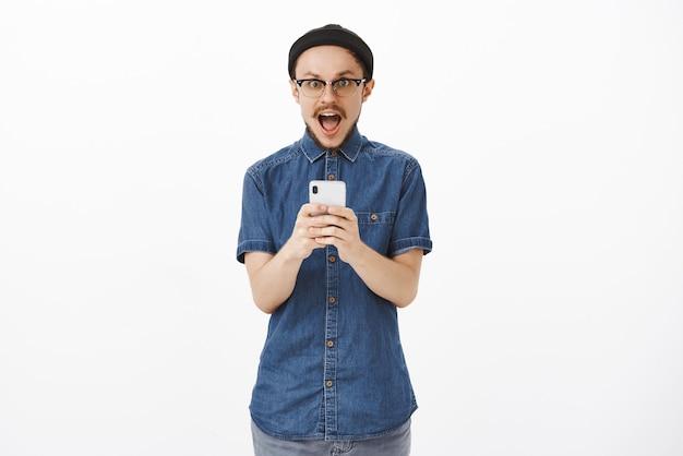 Entusiasta y emocionado guapo modelo masculino creativo con bigote en gafas gorro negro dejando caer la mandíbula de asombro y alegría sosteniendo un teléfono inteligente y recibiendo una oferta increíble increíble Foto gratis