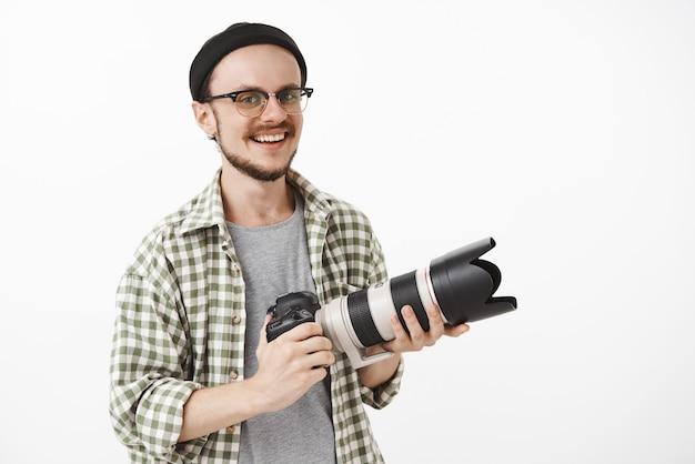 Entusiasta y guapo macho maduro con gafas y gorro negro sosteniendo una cámara profesional y sonriendo con alegría trabajando como periodista o fotógrafo Foto gratis