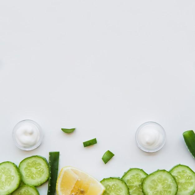 Envase de crema hidratante; aloe vera; rodajas de limón y pepino sobre fondo blanco Foto gratis