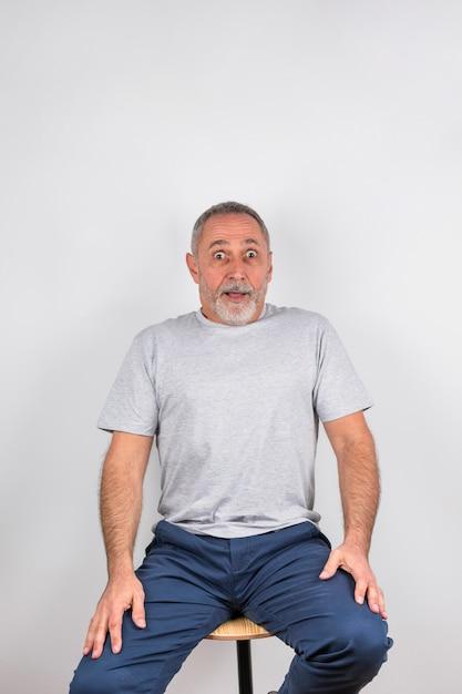 Envejecido hombre sorprendido en silla Foto gratis
