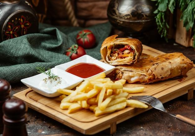 Envoltura de pollo frito con tomate, pimientos, papas fritas, salsas Foto gratis