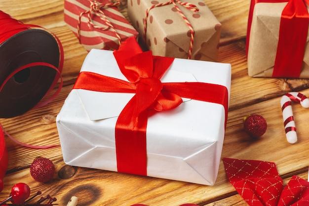 Envolver cajas de regalo con equipos y artículos de decoración sobre fondo de madera Foto Premium
