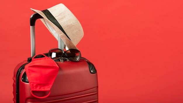Equipaje rojo con sombrero y espacio de copia Foto gratis