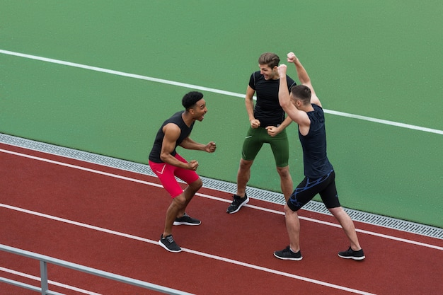 Equipo de atleta multiétnico feliz hacer gesto ganador Foto gratis
