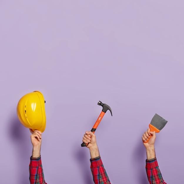 Equipo de construcción contra la pared púrpura Foto gratis