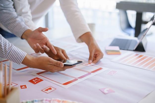 Equipo creativo de diseño de ux que discute el flujo de trabajo de tramas de pantalla de la aplicación móvil. Foto Premium