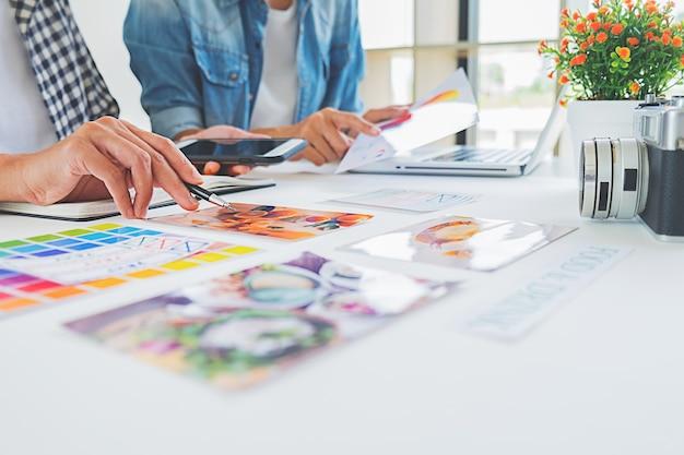 Equipo creativo del lanzamiento del diseñador asiático de la publicidad que discute ideas en oficina. Foto Premium