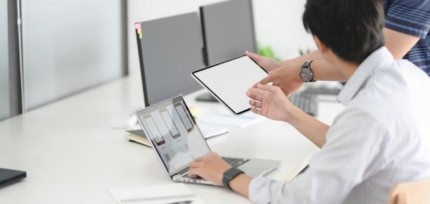 Equipo de desarrollo web ux apasionado joven discutiendo plantilla de teléfono inteligente con computadora portátil Foto Premium