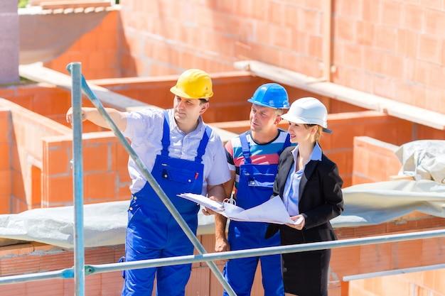 Equipo discutiendo la construcción o los planos del sitio de construcción Foto Premium