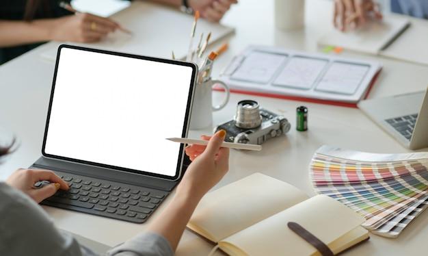 Un equipo de diseñadores profesionales está trabajando con teléfonos inteligentes y computadoras portátiles para diseñar aplicaciones. Foto Premium