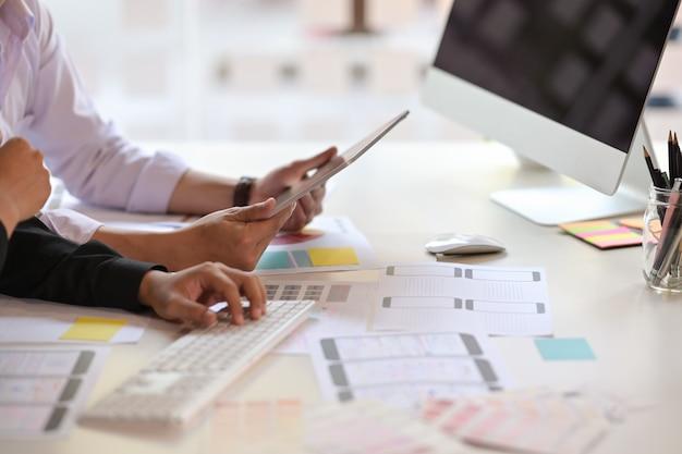 Equipo de diseño de ux que usa una tableta que diseña el diseño de un teléfono móvil con estructura de alambre Foto Premium