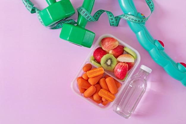 Equipo de entrenamiento. comida sana. concepto de comida sana y estilo de vida deportivo. almuerzo vegetariano pesa de gimnasia, agua, frutas en superficie rosa. vista superior. lay flat Foto gratis