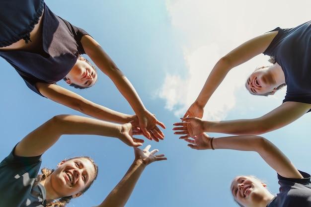 Equipo femenino juntando las manos Foto gratis
