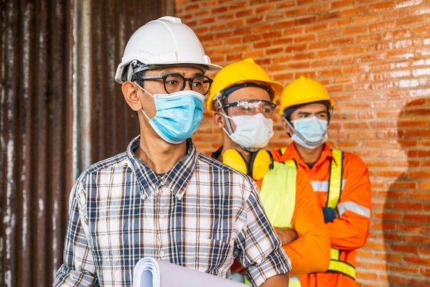 El equipo de ingenieros de construcción y tres arquitectos están listos para usar máscaras médicas. corona o covid-19 usan máscaras durante el diseño de la construcción. Foto Premium