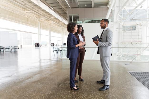 Equipo interracial discutiendo proyecto en pasillo de oficina Foto gratis