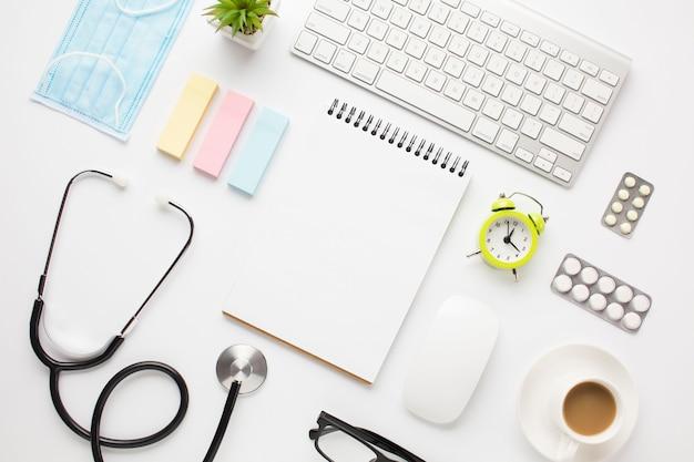 Equipo médico y suministros de oficina con taza de café sobre el escritorio del médico. Foto gratis