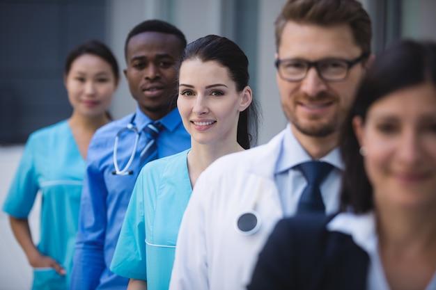 Equipo de médicos de pie en fila Foto gratis