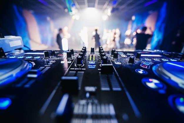 Equipo de música dj en discoteca closeup con gente de baile borrosa Foto Premium