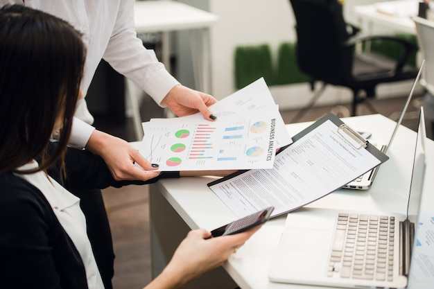 Equipo de negocios analizando gráficos de ingresos con computadoras portátiles modernas. Foto Premium