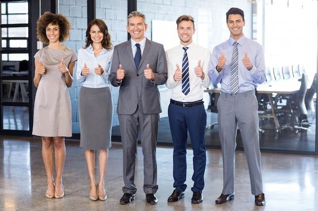 Equipo de negocios exitoso que levanta sus pulgares mientras celebra la victoria en la oficina Foto Premium
