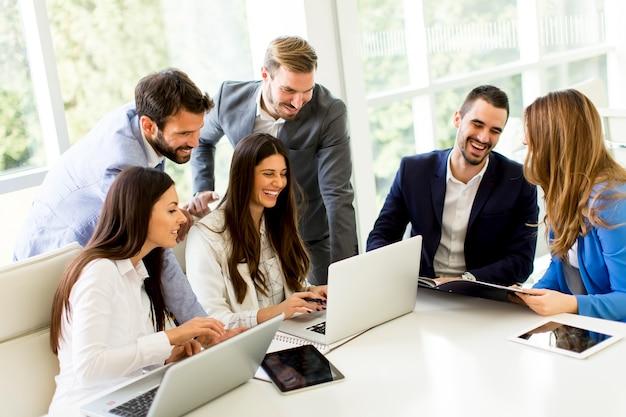 Equipo de negocios de inicio en la reunión en el interior de la oficina moderna brillante y trabajando en la computadora portátil Foto Premium