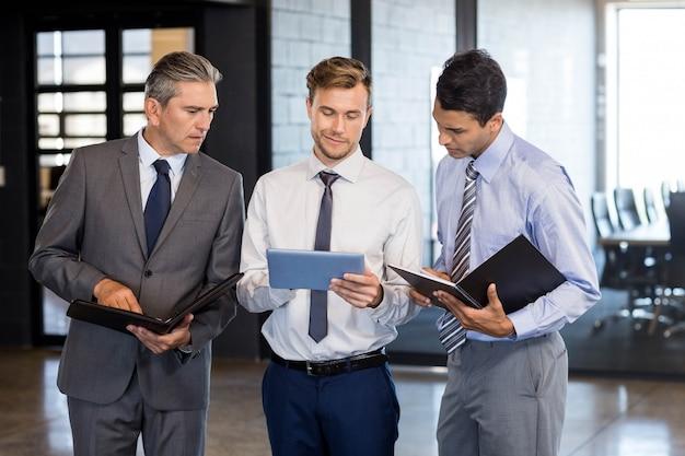 Equipo de negocios interactúa usando tableta digital y organizador en la oficina. Foto Premium