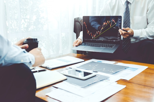 Equipo de negocios inversión emprendedor comercio discutiendo y analizando gráfico bursátil Foto Premium