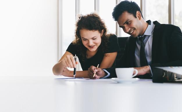 Equipo de negocios joven feliz discutiendo sobre hojas de datos en el escritorio mientras pequeña reunión Foto Premium