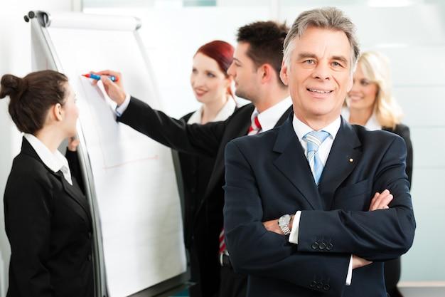 Equipo de negocios con líder en oficina Foto Premium