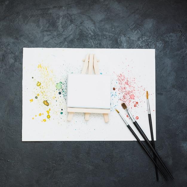 Equipo de pintura y papel de pintura manchada sobre superficie negra. Foto gratis