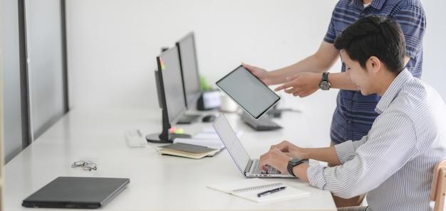 Equipo profesional de desarrolladores web de iu trabajando juntos en su proyecto en un lugar de trabajo moderno Foto Premium