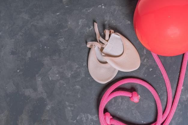 Equipo rítmico de qymnastic. rosa cuerda de saltar, pelota y zapatos de gimnasia vista superior sobre fondo gris Foto Premium