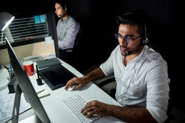Equipo de soporte técnico asiático trabajando turno nocturno en call center Foto Premium