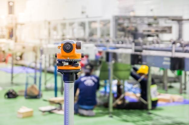 Equipo del topógrafo de la construcción herramienta del nivel del teodolito durante los trabajadores que instalan la máquina Foto Premium