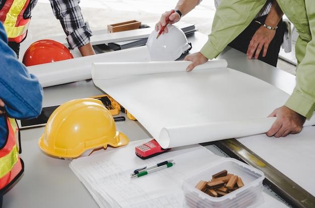 Equipo del trabajador de construcción que planea sobre plan de construcción con el modelo, casco de seguridad Foto Premium