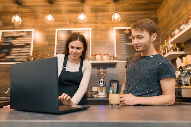 Equipo de trabajadores de cafeterías trabajando cerca del mostrador con laptop Foto Premium