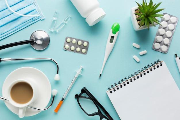 Equipos médicos incluyendo anteojos y medicamentos en el escritorio. Foto gratis