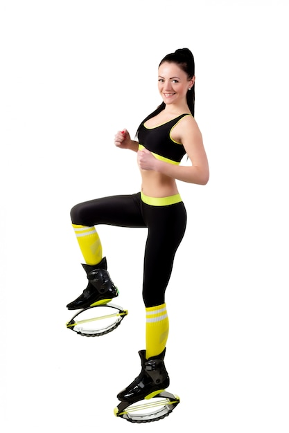 Esbelta niña sonriente en zapatos kangoo jamps haciendo ejercicios, Foto Premium