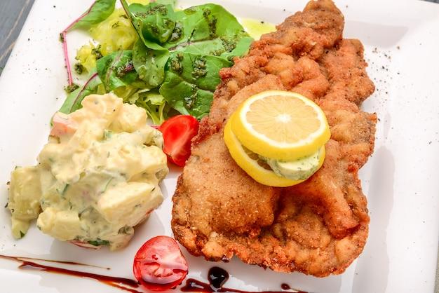 Escalope vienés con ensalada de patata y limón Foto Premium