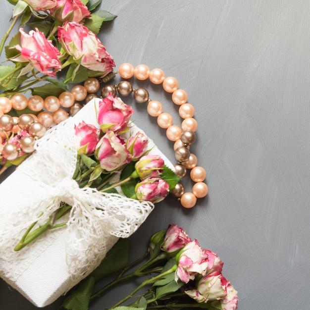 Escena plana para mujer puesta rosas flores, regalo y collar en gris neutro. vista superior. Foto Premium