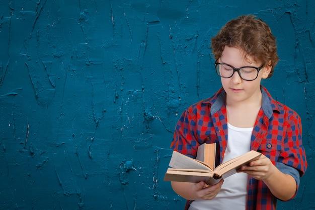 Escolar elemental lindo que sostiene el libro Foto Premium