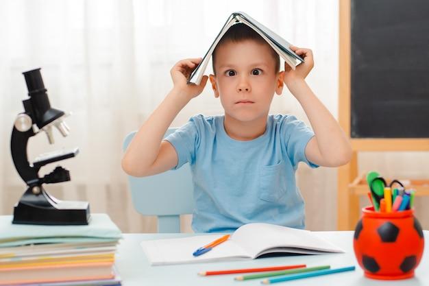 Escolar sentado en casa aula acostado escritorio lleno de libros material de capacitación escolar durmiendo perezoso Foto Premium