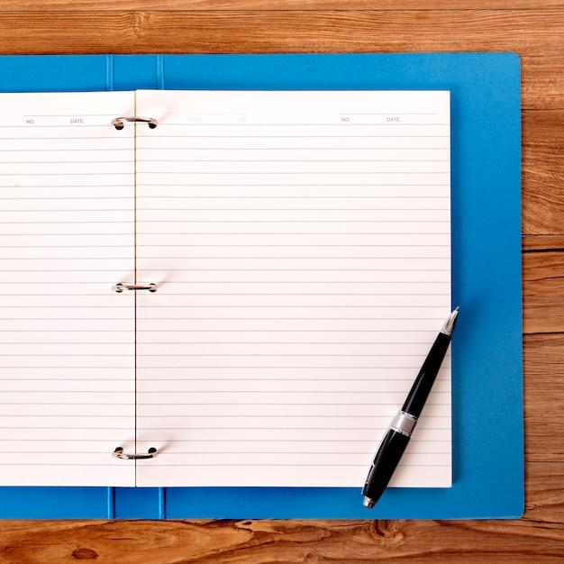 Escritorio del alumno con carpeta de proyecto azul Foto gratis