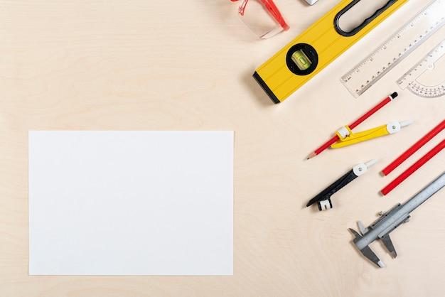 Escritorio de arquitecto con vista superior de la hoja de papel Foto gratis
